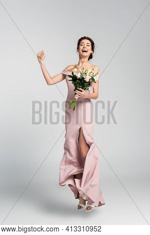 Full Length View Of Excited Fiancee Holding Wedding Bouquet While Jumping On Grey.