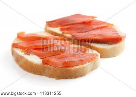 Sandwiches with smoked trout on white surface with shadow - isolated