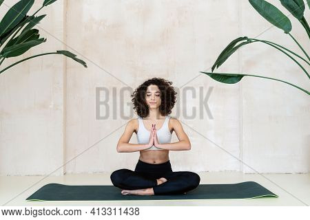 Peaceful African American Woman In Black Sportswear Sitting On Fitness Mat In Meditation Pose With P