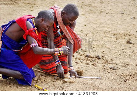 young Masai warriors shows how to make fire