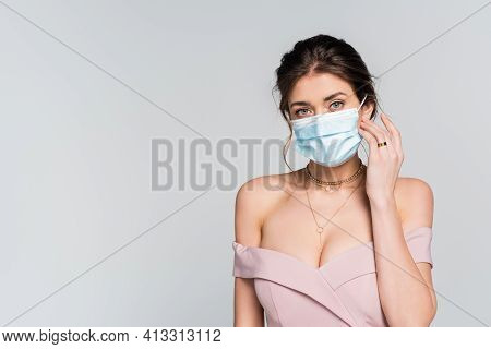 Elegant Fiancee Looking At Camera While Touching Medical Mask Isolated On Grey.
