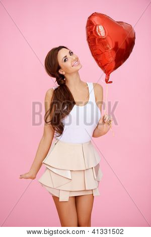 Vivacious sexy woman with a red heart balloon for her Valentine's Day, wedding, engagement or anniversary party celebrations