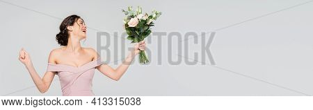 Excited Fiancee Showing Win Gesture While Holding Wedding Bouquet Isolated On Grey, Banner.