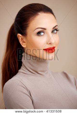 Beautiful glamorous young woman in a stylish polo neck with vivid red lipstick and her long brunette hair tied back neatly in a ponytail on a beige studio background