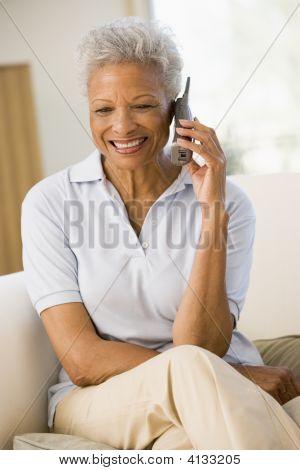 Vrouw zitten In levende kamer met behulp van telefoon- en glimlachen