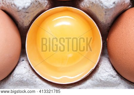A Brown Chicken Egg Is Half Broken Among Other Eggs In A Carton Tray Close Up