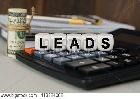 Business And Finance Concept. There Are Cubes On The Calculator That Say - Leads. Nearby Out Of Focu