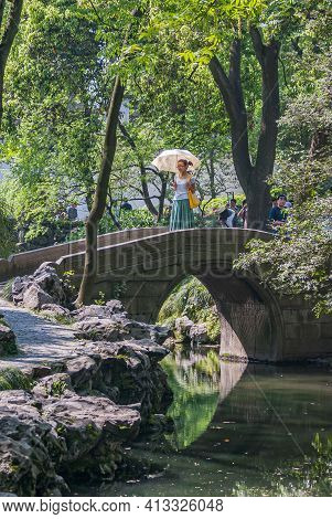 Suzhou, China - May 3, 2010: Humble Administrators Garden.  Young Woman With White Umbrella Stans On