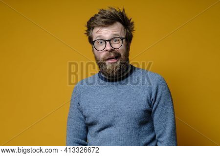A Strange Shaggy Man With Glasses, With A Stupid Expression On His Face, Looks At The Camera In Bewi