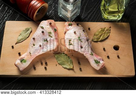 Сhicken Legs On A Cutting Board With Spices. The Idea Of Cooking Lunch Or Breakfast In A Restaurant.