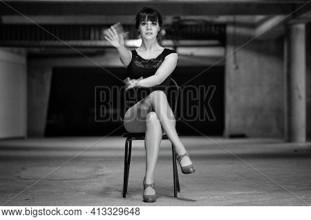 Amazing Beautiful And Sensual Dancer Sitting On A Chair, In A Cabaret Style,  And Waving With Her Ha
