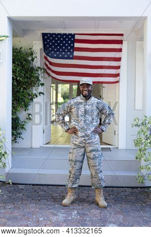 Smiling african american male soldier standing in front of american flag outside home. soldier returning home to family.