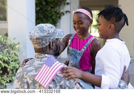 African american soldier father greeting smiling son and daughter in front of house. soldier returning home to family.