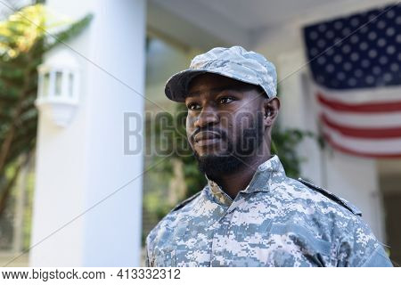 Portrait of african american male soldier standing in front of american flag outside home. soldier returning home to family.