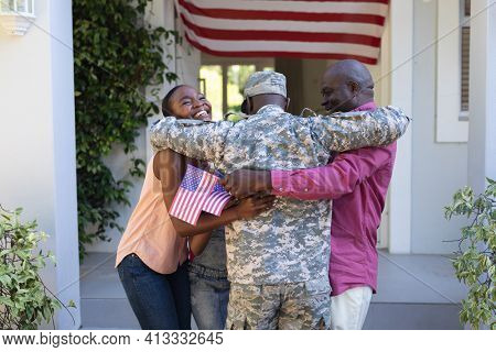 African american soldier father hugging smiling wife and father in front of house and american flag. soldier returning home to family.