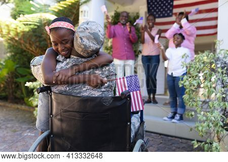 African american soldier father in wheelchair hugging daughter three generation family behind. soldier returning home to family.