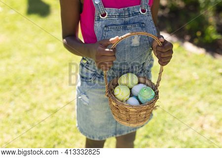 Midsection of african american girl holding basket while easter egg hunting. celebrating easter at home in isolation during quarantine lockdown.