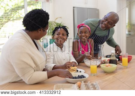 African american grandparents teaching girl and boy cooking in the kitchen. family spending quality time together.