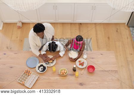 High angle view of african american grandmother teaching grandchildren cooking in the kitchen. family spending quality time together.