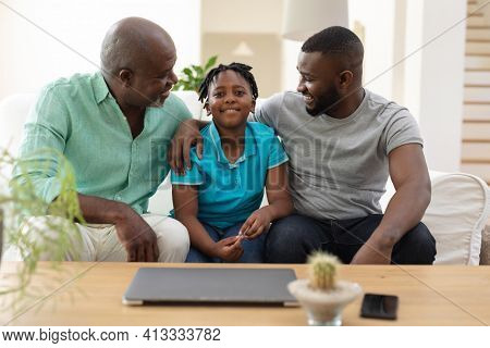 Senior african american grandfather sitting on couch smiling with adult son and grandson. happy three generation family spending time together at home.