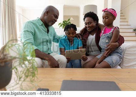 Happy african american grandfather and grandmother on couch with grandchildren looking at tablet. happy family spending time together at home.
