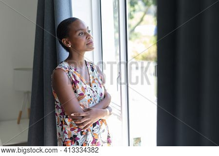 African american woman with short hair standing looking out of window and thinking. staying at home in isolation during quarantine lockdown.