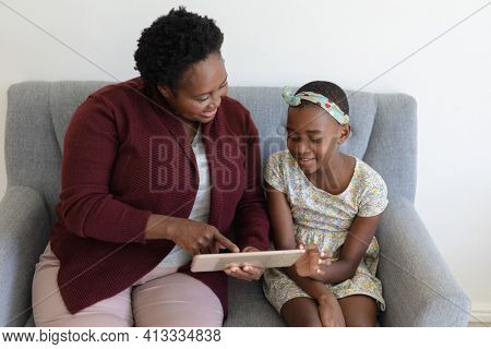Senior african american grandmother sitting on couch beside smiling granddaughter using tablet. happy family spending time together at home.