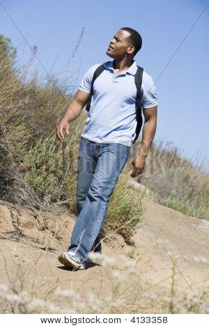Homem andando no caminho para a praia