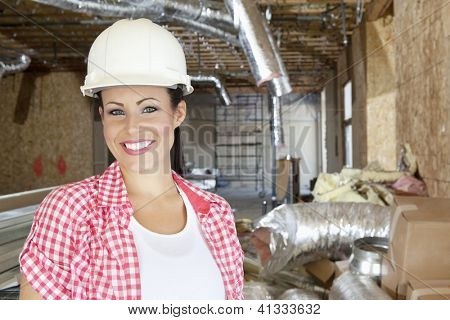 Close-up portrait of smiling young woman contractor at construction site