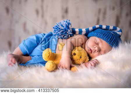 Newborn boy peacefully sleeping with his softy teddy bear