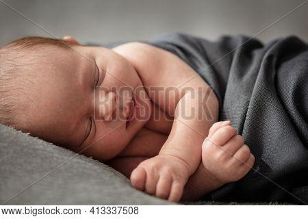 Newborn baby warping in blanket  peacefully sleeping