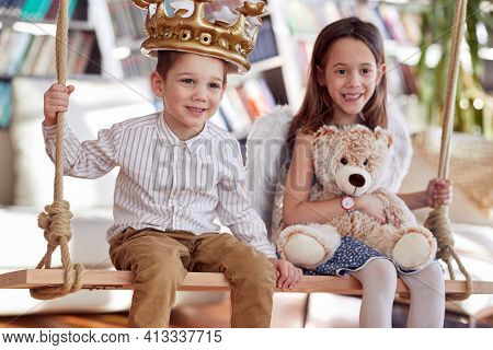 Cute little brother and sister is sitting on the swing while playing in a cheerful atmosphere at home. Family, home, playtime