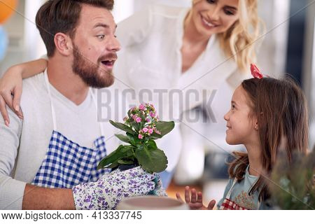 A young happy family spending a quality time while planting flowers in a cheerful atmosphere at home together. Family, home, playtime