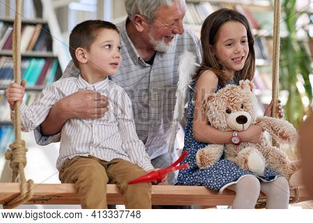 Grandchildren are sitting on the swing and playing with their grandfather in a playful atmosphere at home. Family, home, playtime