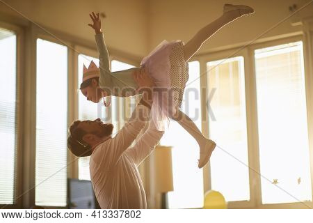 A young father holding his little ballerina in the air while they are practicing ballet moves at a training in a playful atmosphere at home. Family, ballet, training