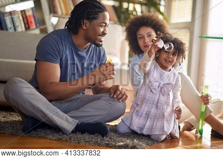 A cute little girl enjoying making soap bubbles with her parents in a playful atmosphere at home. Family, together, playtime