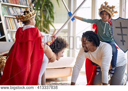 Children dressed as knights are riding their parents while playing knights game in a cheerful atmosphere at home. Family, home, playtime
