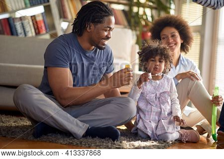 Young parents and their little daughter sitting on the floor in a relaxed atmosphere at home and enjoy making soap bubbles. Family, home, playtime
