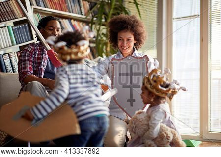 Young parents and their kids enjoying knight fight game while playing in a cheerful atmosphere at home together. Family, home, playtime