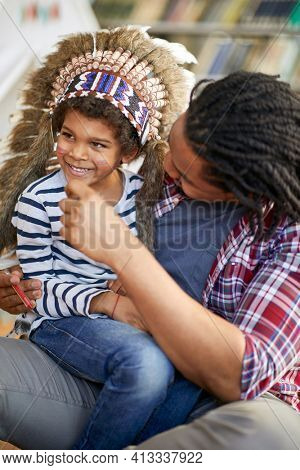 A little boy dressed like an Indian sitting in his father lap who made indian colors on his face in a playful atmosphere at home. Family, home, playtime