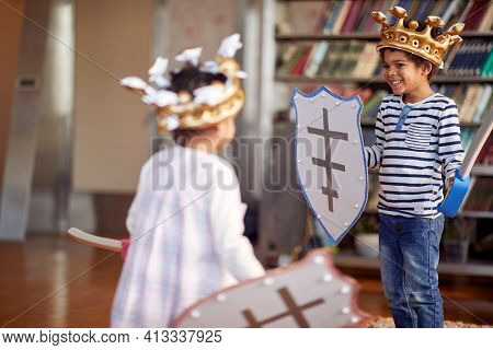 A little brother and sister dressed like knights are having swords fight game while playing in a cheerful atmosphere at home. Family, home, playtime
