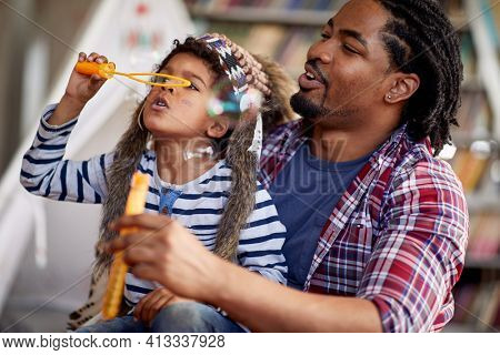 A little boy dressed like an Indian enjoys making soap bubbles with his father ina playful atmosphere at home. Family, home, playtime