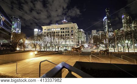 Calgary Alberta Canada, March 15 2021: A Quiet Downtown Plaza At Night With Horse Sculptures And Dow