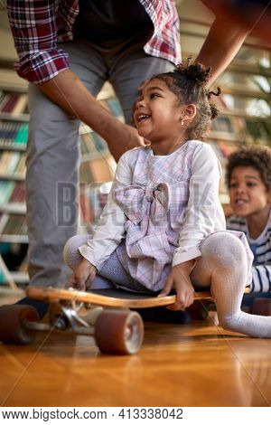 A cute little girl sitting on the skateboard in a cheerful atmosphere at home and playing with her father and little brother. Family, home, playtime