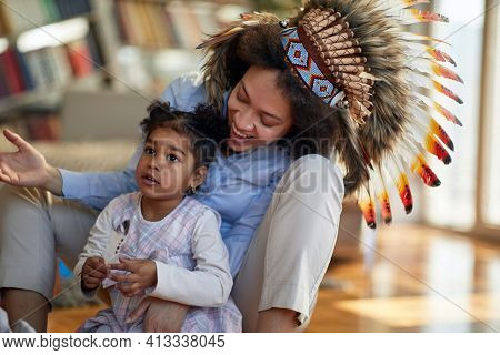 A young mother with indian war bonnet sitting on the floor in a cheerful atmosphere at home and playing with her little daughter. Family, home, playtime