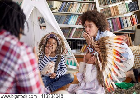 Children with Indian war bonnets are yelling and imitate Indians while playing with their parents in a cheerful atmosphere at home. Family, home, playtime