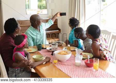 African american grandfather taking selfie with grandchildren and their parents at family meal. three generation family spending quality time together.