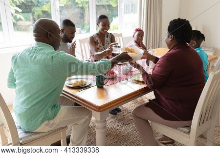 Happy african american parents, grandparents and grandchildren at table serving food and eating. three generation family spending quality time together.