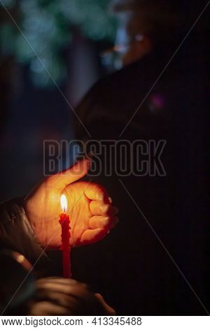 Woman Holds Candle In Her Hand, Covering The Flame From The Wind With Her Palm, In Memory Of The Dea