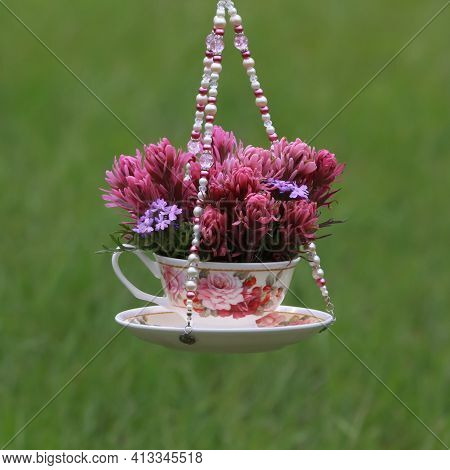 Pink And Purple Flowers In A Teacup Vase Hanging In The Garden